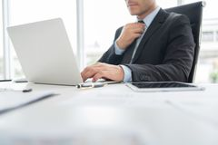 Confident Businessman is working on Laptop computer. stock photos