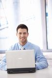Confident businessman working on laptop smiling Royalty Free Stock Photo