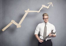 Confident businessman with wrench and graph. Concept: Building your own successful career or business. Young confident businessman holding  wrench in front of Royalty Free Stock Images