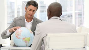 Confident businessmen looking at a terrestrial globe stock footage