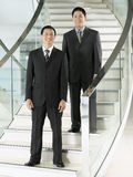 Confident Businessmen Standing On Stairs. Full length portrait of two confident businessmen standing on stairs Stock Photos