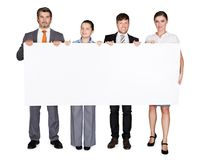 Confident businesspeople displaying large billboard Royalty Free Stock Photos