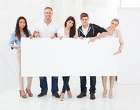 Confident businesspeople holding blank billboard Royalty Free Stock Image