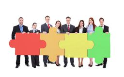 Confident businesspeople joining jigsaw puzzle pieces. Full length portrait of confident businesspeople joining jigsaw puzzle pieces against white background Royalty Free Stock Photos