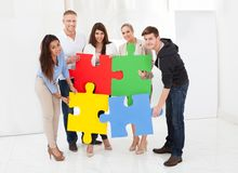 Confident businesspeople joining puzzle pieces Royalty Free Stock Photos