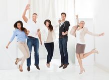 Confident businesspeople jumping with arms raised Stock Photography