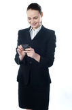 Confident businessperson messaging. And smiling Stock Photography