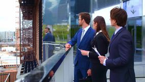 Confident businesspersons talking in front of modern office building. Businessmen and businesswoman have business. Conversation. Banking, professional job and stock video