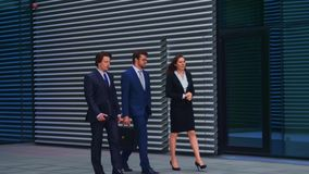 Confident businesspersons talking in front of modern office building. Businessmen and businesswoman have business. Conversation. Banking, professional job and stock footage