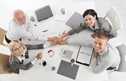 Confident businessteam holding hands at meeting Royalty Free Stock Photos