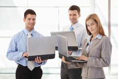 Confident businessteam working on laptop smiling Stock Images