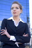 Confident Businesswoman. Portrait of a confident young businesswoman with her arms folded in front of her, looking up and away to her right.  Taken outdoors Stock Image