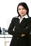 Confident businesswoman. Situated in office, a business woman stand confidently in front of her working desk Stock Photography