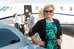 Confident Businesswoman Against Private Jet Stock Image
