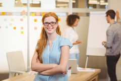 Confident businesswoman with arm crossed with colleagues in background Stock Photo