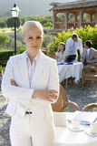 Confident businesswoman with arms crossed at caf? with coworkers in background Royalty Free Stock Images