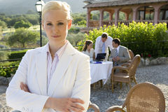 Confident businesswoman with arms crossed at caf? with coworkers in background Royalty Free Stock Image