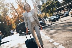 Confident businesswoman. Beautiful young woman in suit pulling luggage and smiling while walking outdoors royalty free stock photos