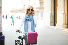 Confident businesswoman with bike in the street Royalty Free Stock Photo