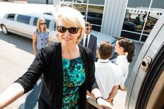 Confident Businesswoman Boarding Private Jet. Mature businesswoman boarding private jet with colleagues; airhostess and pilot at airport terminal Stock Photography
