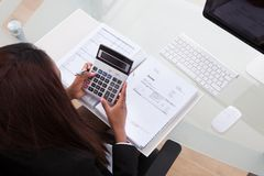 Confident businesswoman calculating tax at desk Stock Photography