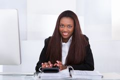 Confident businesswoman calculating tax at desk Stock Photos