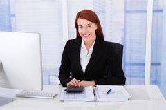 Confident businesswoman calculating tax Royalty Free Stock Photo
