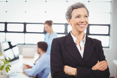 Confident businesswoman with colleague in background Royalty Free Stock Images