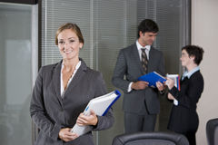 Confident businesswoman, colleagues in background Stock Photos