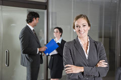 Confident businesswoman, colleagues in background Royalty Free Stock Photos