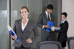 Confident businesswoman, colleagues in background Royalty Free Stock Images