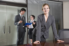 Confident businesswoman, colleagues in background Stock Images