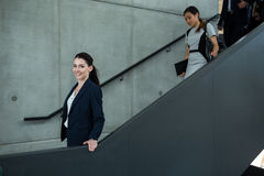 Confident businesswoman with colleagues climbing down the stairs Royalty Free Stock Photography