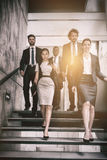 Confident businesswoman with colleagues climbing stairs. In office Royalty Free Stock Photos