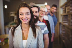 Confident businesswoman with colleagues standing in row. Portrait of confident young businesswoman with colleagues standing in row at creative office Stock Image