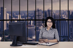 Confident businesswoman with computer and paperwork Stock Photo