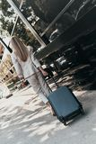 Confident businesswoman. Full length rear view of young woman in suit pulling luggage while walking outdoors royalty free stock photo