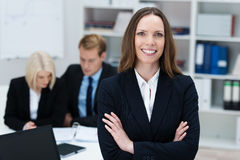 Confident businesswoman with folded arms. Confident attractive young businesswoman standing with folded arms in a busy office smiling at the camera Stock Image