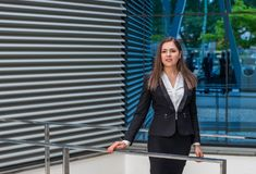Confident businesswoman in front of modern office building. Business, banking, corporation and financial market concept. Confident businesswoman in front of royalty free stock images