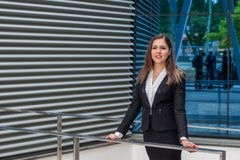 Confident businesswoman in front of modern office building. Business, banking, corporation and financial market concept. Confident businesswoman in front of royalty free stock photography