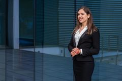Confident businesswoman in front of modern office building. Business, banking, corporation and financial market concept. Confident businesswoman in front of stock images