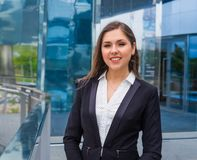Confident businesswoman in front of modern office building. Business, banking, corporation and financial market concept. Confident businesswoman in front of royalty free stock image
