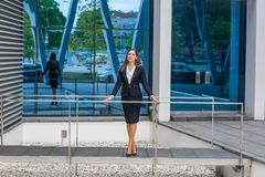 Confident businesswoman in front of modern office building. Business, banking, corporation and financial market concept. Confident businesswoman in front of stock photography