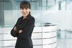 Confident Businesswoman In Front Of Reception Desk Stock Photography