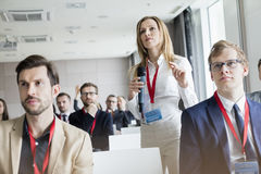 Confident businesswoman gesturing while holding microphone during seminar stock image