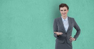 Confident businesswoman gesturing over green background. Digital composite of Confident businesswoman gesturing over green background royalty free stock image