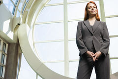 Confident businesswoman, with ginger hair, wearing grey suit, standing beside window, portrait, low angle view Royalty Free Stock Photos