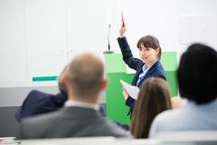 Businesswoman Giving Presentation To Colleagues In Seminar Hall. Confident businesswoman giving presentation to colleagues in seminar hall Stock Photography