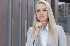Confident businesswoman with hand on chin looking away against office building Stock Image