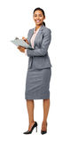 Confident Businesswoman Holding Clipboard. Full length portrait of confident businesswoman holding clipboard against white background. Vertical shot Royalty Free Stock Photography